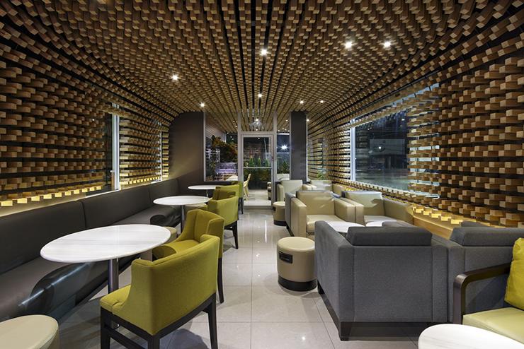 """""""McCafé El Zapote presenta un espacio abierto rodeado de una piel tridimensional uniforme, formada por miles de bloques de madera que expresan tres conceptos principales.""""  Mc Café el Zapote 13"""