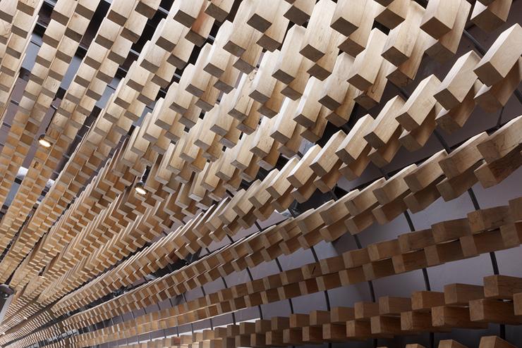 """""""McCafé El Zapote presenta un espacio abierto rodeado de una piel tridimensional uniforme, formada por miles de bloques de madera que expresan tres conceptos principales.""""  Mc Café el Zapote 23"""
