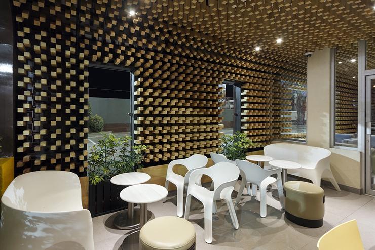"""""""McCafé El Zapote presenta un espacio abierto rodeado de una piel tridimensional uniforme, formada por miles de bloques de madera que expresan tres conceptos principales.""""  Mc Café el Zapote 31"""