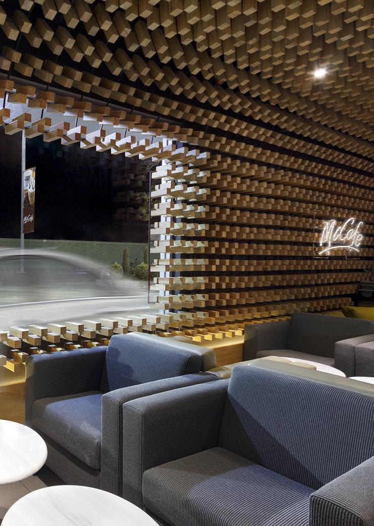 """""""McCafé El Zapote presenta un espacio abierto rodeado de una piel tridimensional uniforme, formada por miles de bloques de madera que expresan tres conceptos principales.""""  Mc Café el Zapote 4"""
